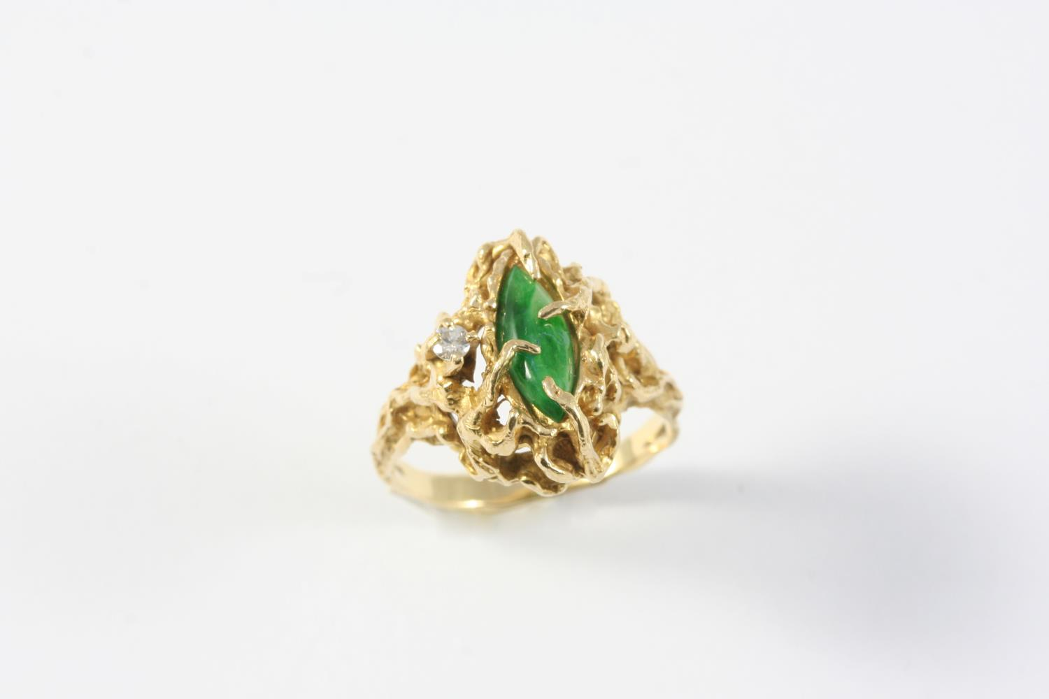 A JADE AND DIAMOND RING the marquise-shaped jade is set with a circular-cut diamond in openwork