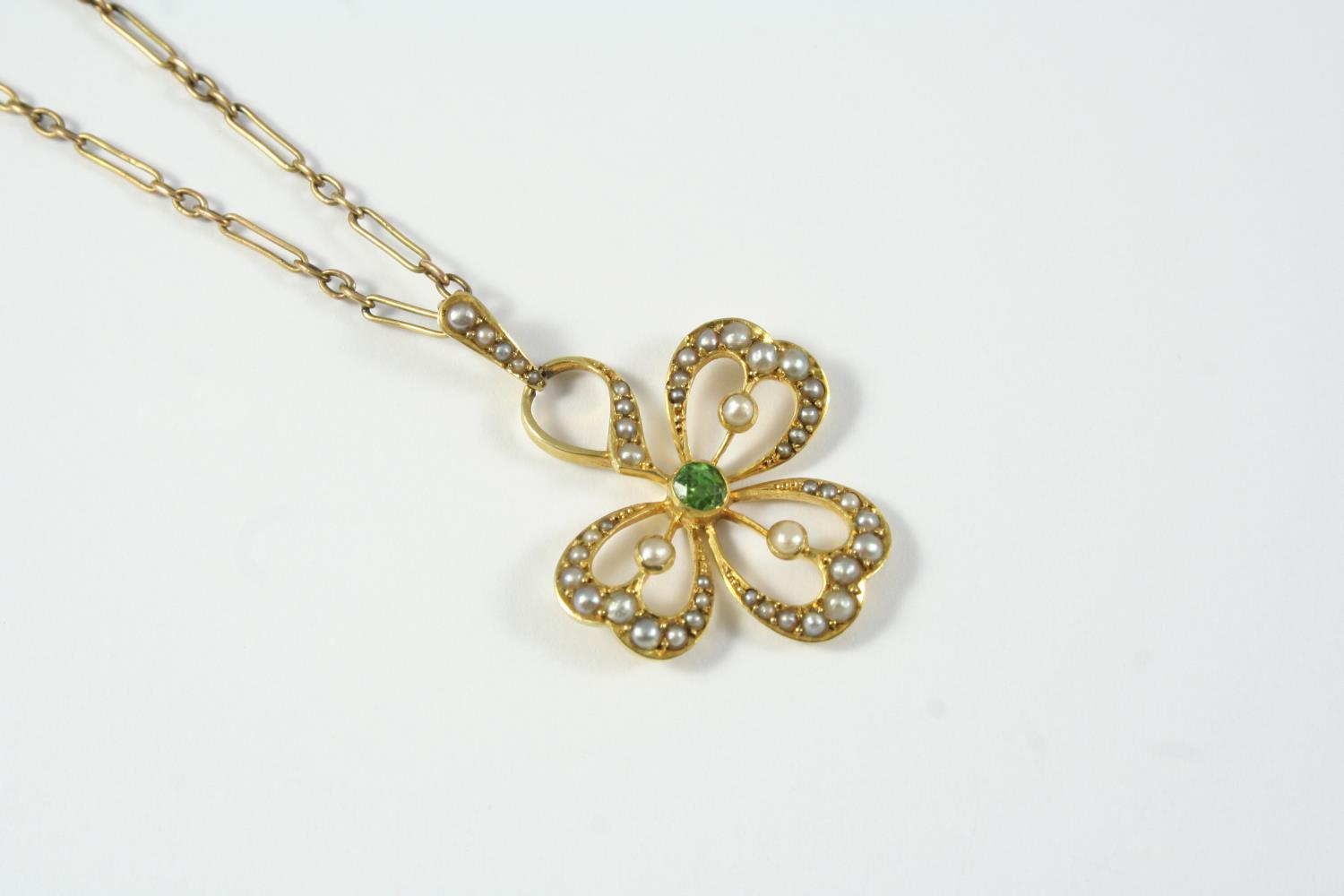 AN EDWARDIAN PERIDOT AND SEED PEARL PENDANT the openwork three leaf clover mount is centred with a
