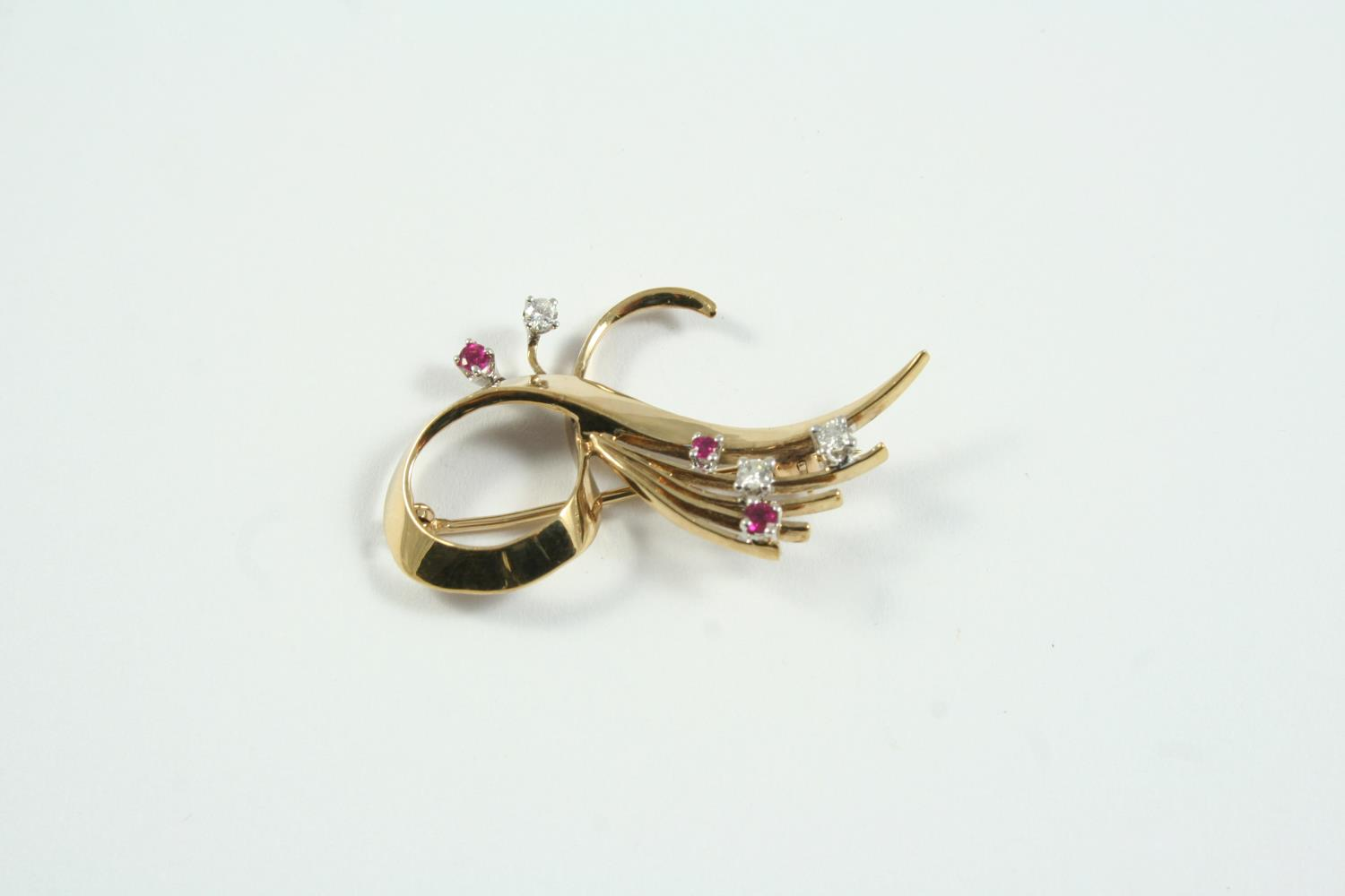 A GOLD, RUBY AND DIAMOND BROOCH the yellow gold scrolling mount is set with circular-cut rubies