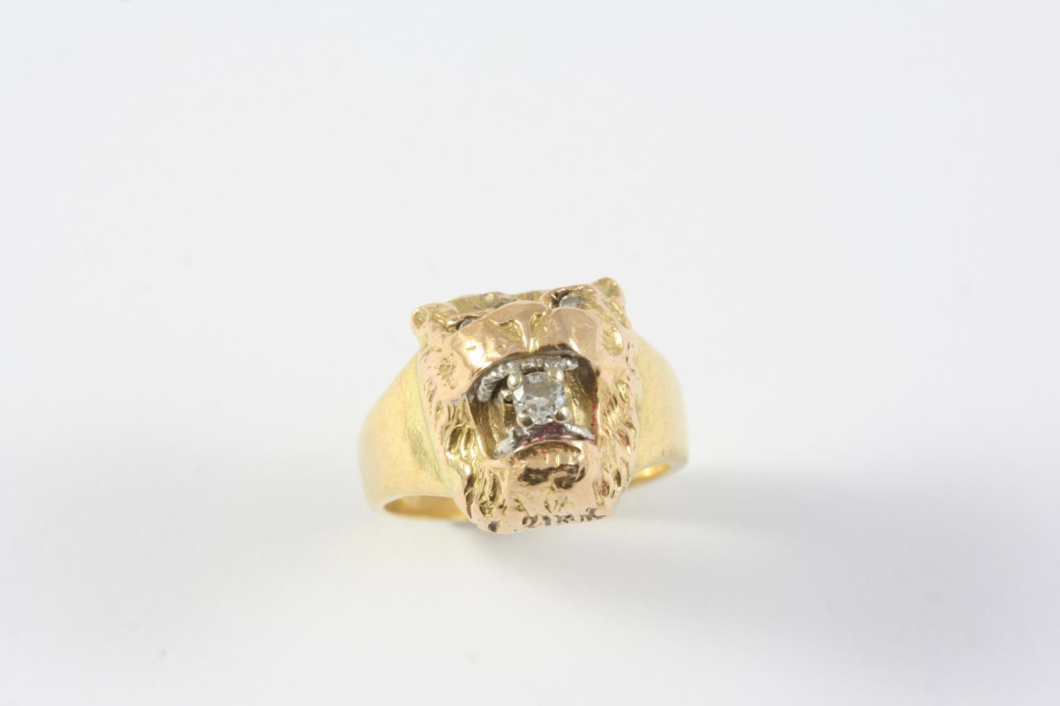 A GOLD AND DIAMOND LION MASK RING realistically formed, with diamond set eyes, holding a circular-