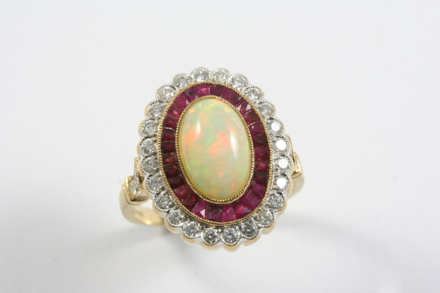 AN OPAL, RUBY AND DIAMOND CLUSTER RING the oval-shaped white opal is set within a surround of