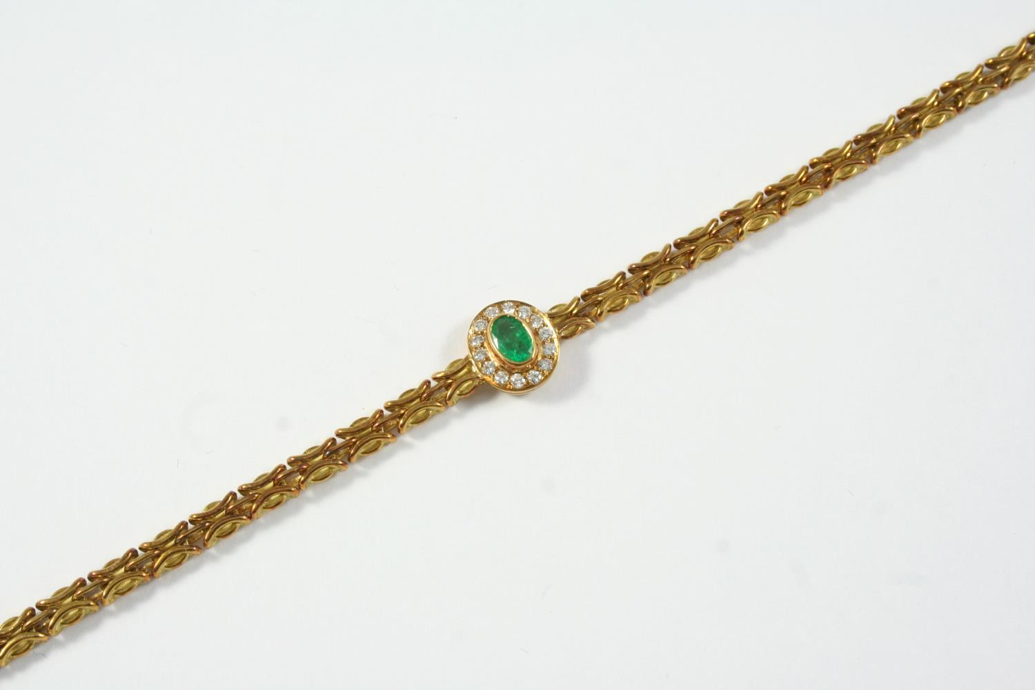 A GOLD, EMERALD AND DIAMOND BRACELET the yellow gold fancy link bracelet is mounted with an