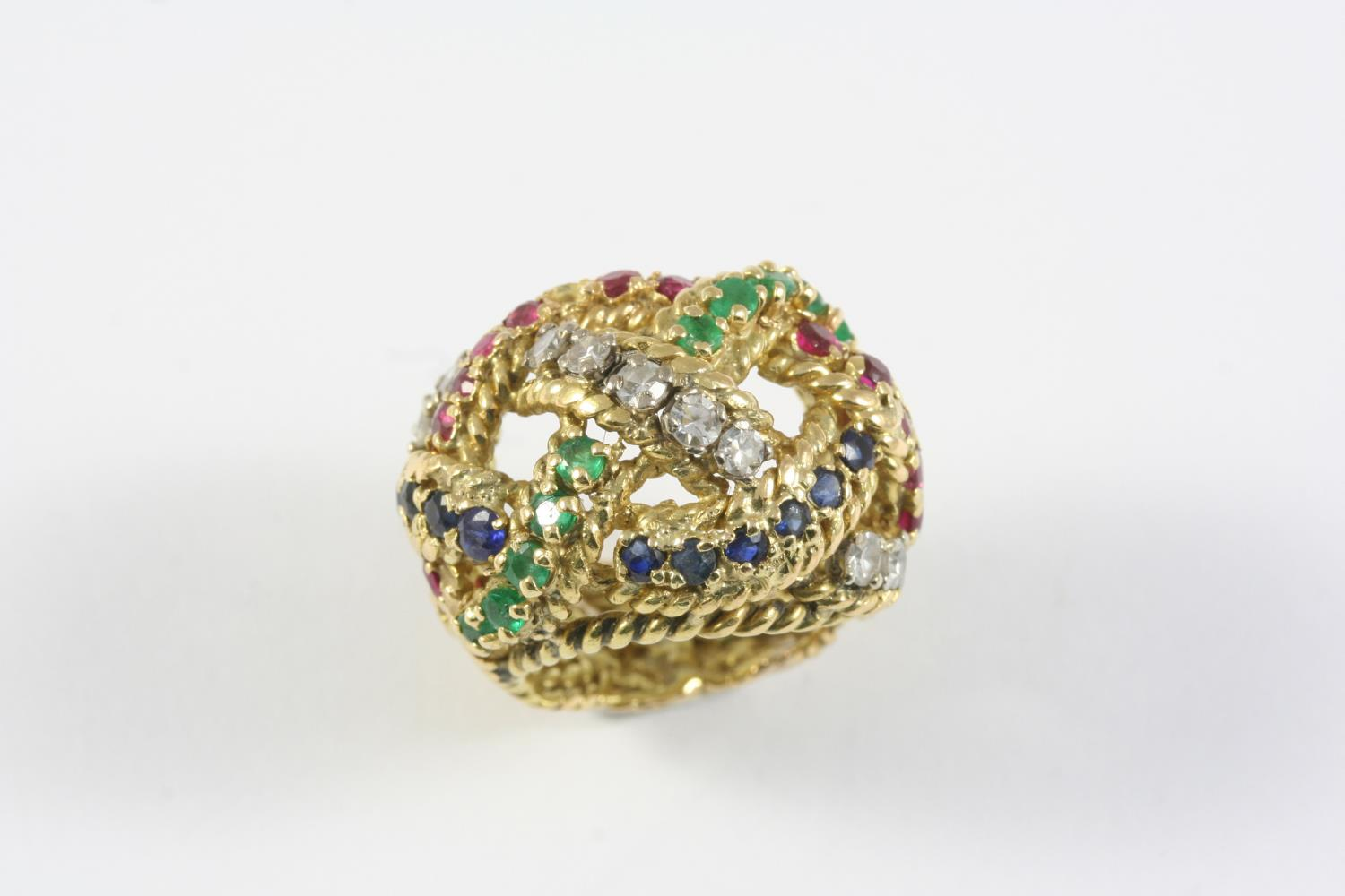 A GOLD AND GEM SET RING the woven openwork design is mounted with circular-cut diamonds, emeralds,