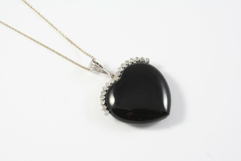 A BLACK ONYX AND DIAMOND HEART-SHAPED PENDANT the heart-shaped black onyx mounted with collet set
