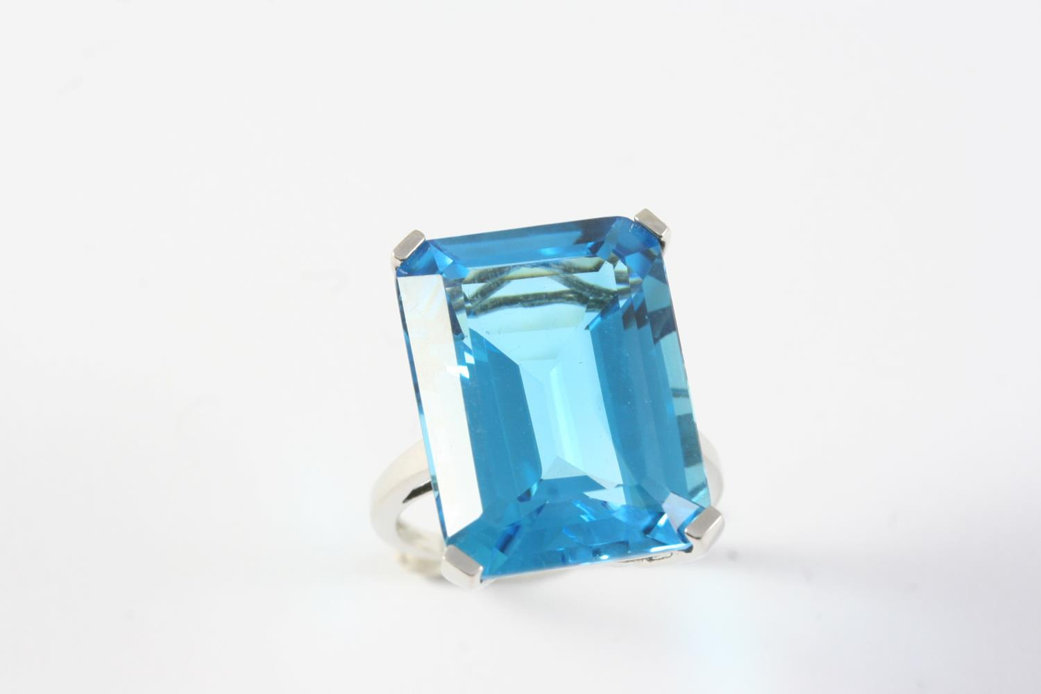 A BLUE TOPAZ SINGLE STONE RING the step-cut blue topaz weighs approximatey 25.0 carats is set in