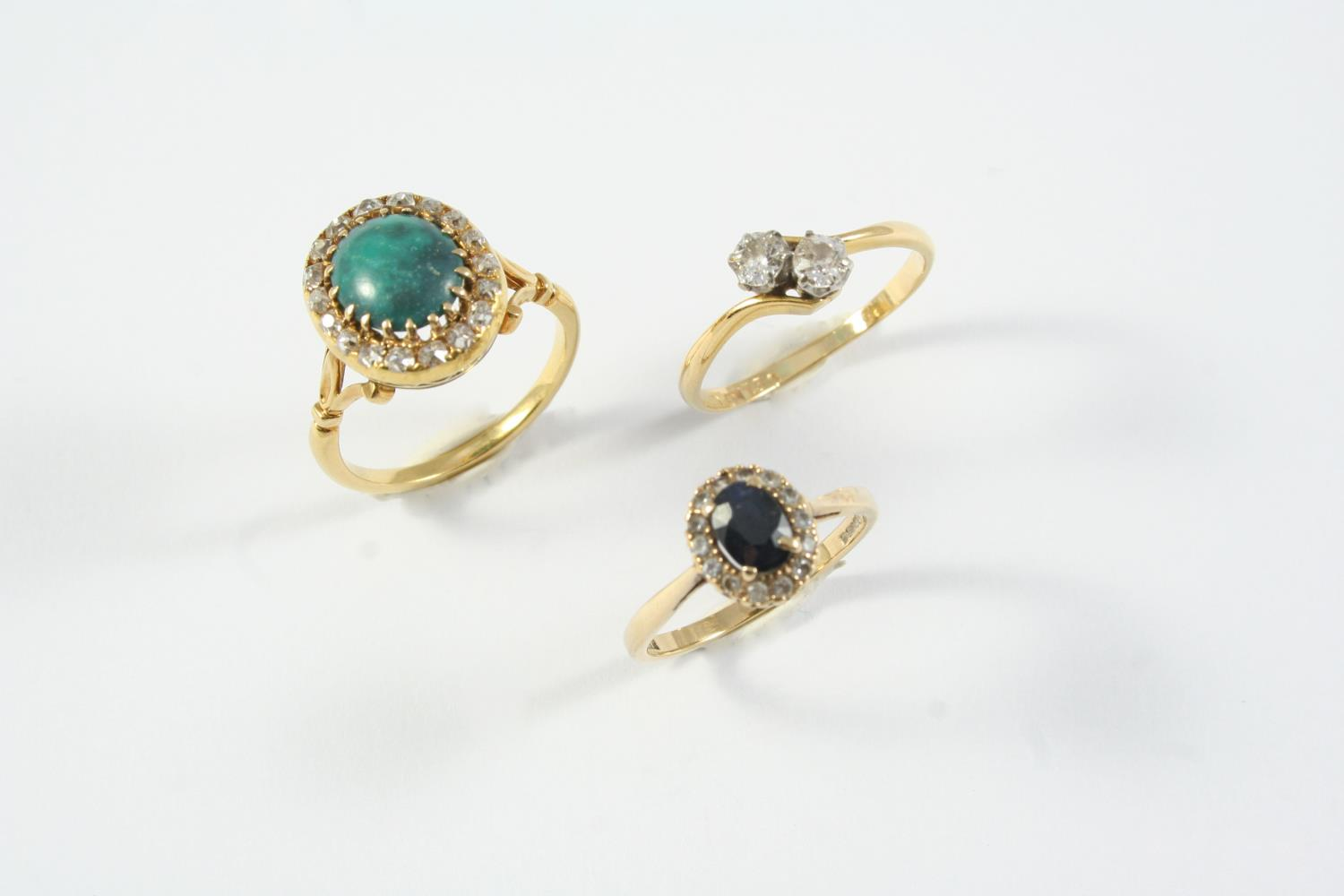 A SAPPHIRE AND DIAMOND CLUSTER RING the oval-shaped sapphire is set within a surround of circular-