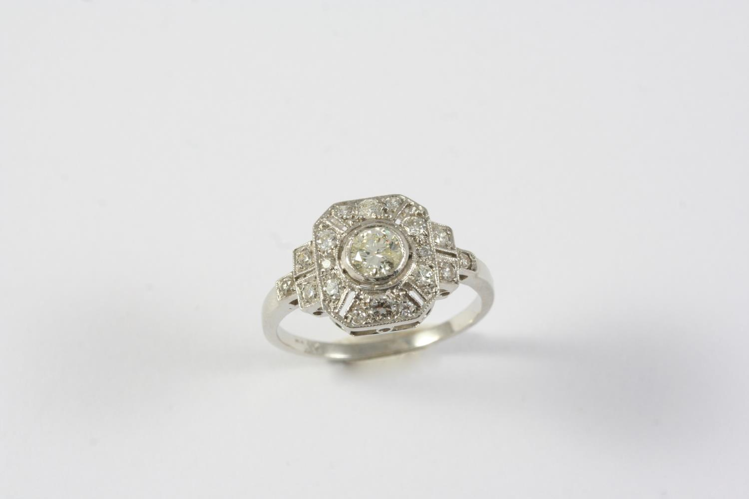 A DIAMOND CLUSTER RING the circular-cut diamond is collet set within a surround of smaller
