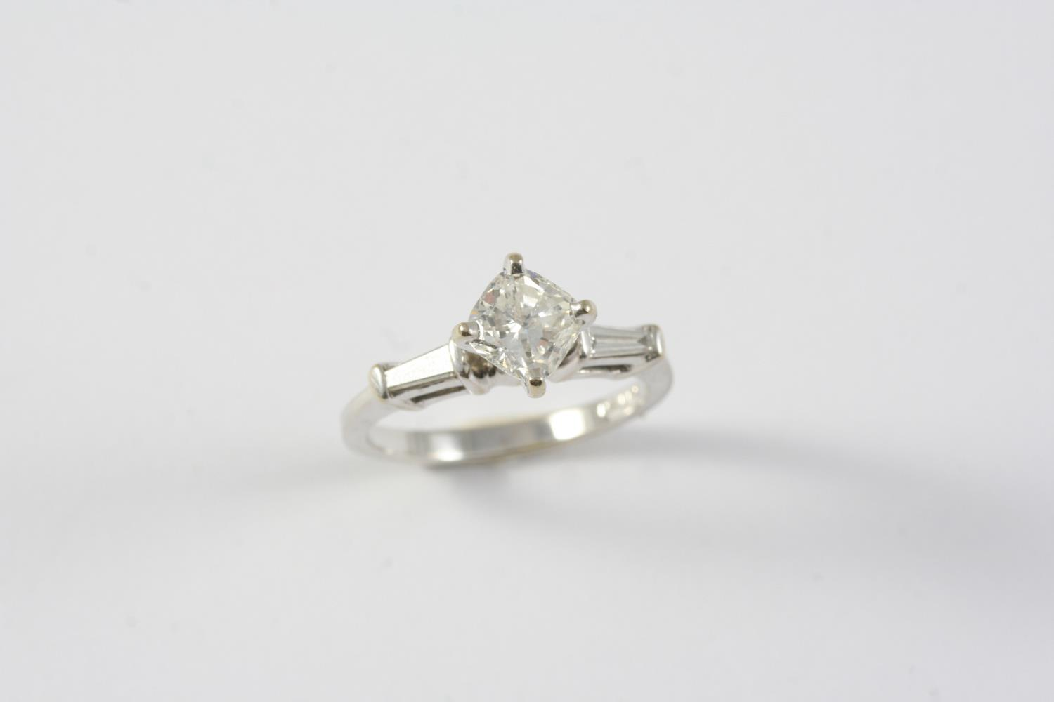 A DIAMOND SOLITARIE RING the cushion-shaped diamond is set with a tapered baguette-cut diamond to