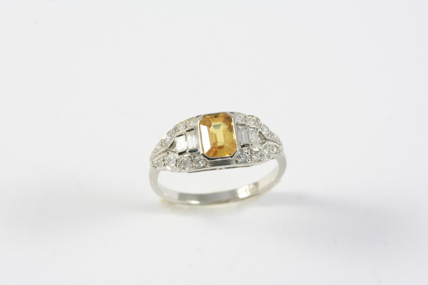 A YELLOW SAPPHIRE AND DIAMOND RING the cut cornered rectangular-shaped yellow sapphire is set within