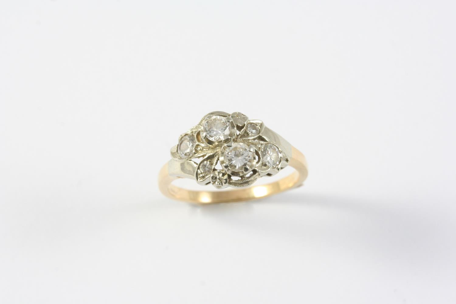 A DIAMOND RING mounted with four circular-cut diamonds and two smaller diamonds, in gold. Size O