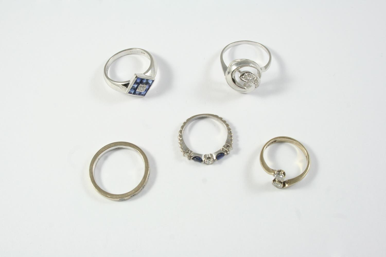 FIVE ASSORTED GOLD AND GEM SET RINGS including a diamond cross-over ring, set with two circular-