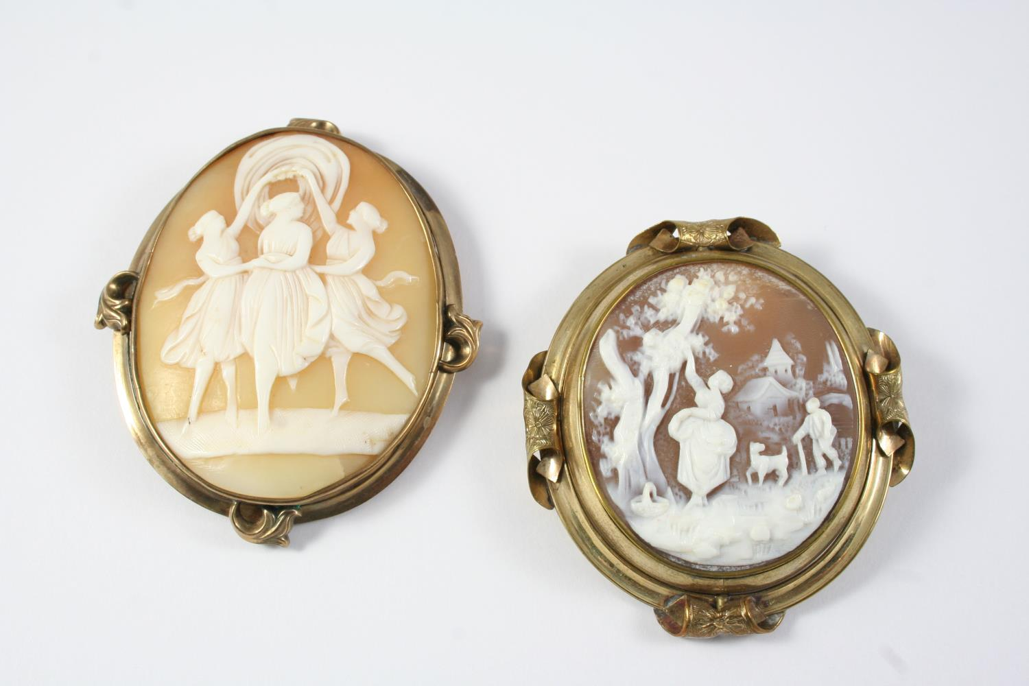 A CARVED SHELL CAMEO BROOCH depicting The Three Graces, in a gold mount, 6.5 x 5.5cm., together with
