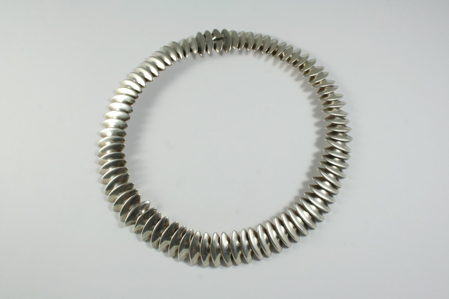 A SILVER NECKLACE BY GEORG JENSEN designed by Hans Hansen, formed with inter-linking discs, with
