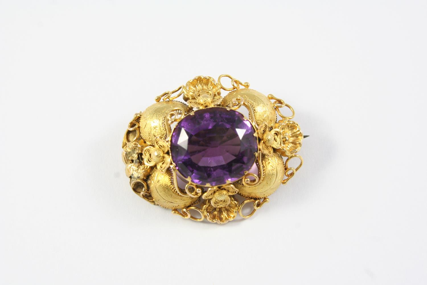 A VICTORIAN AMETHYST AND GOLD BROOCH the oval-shaped amethyst is set within an ornate foliate and
