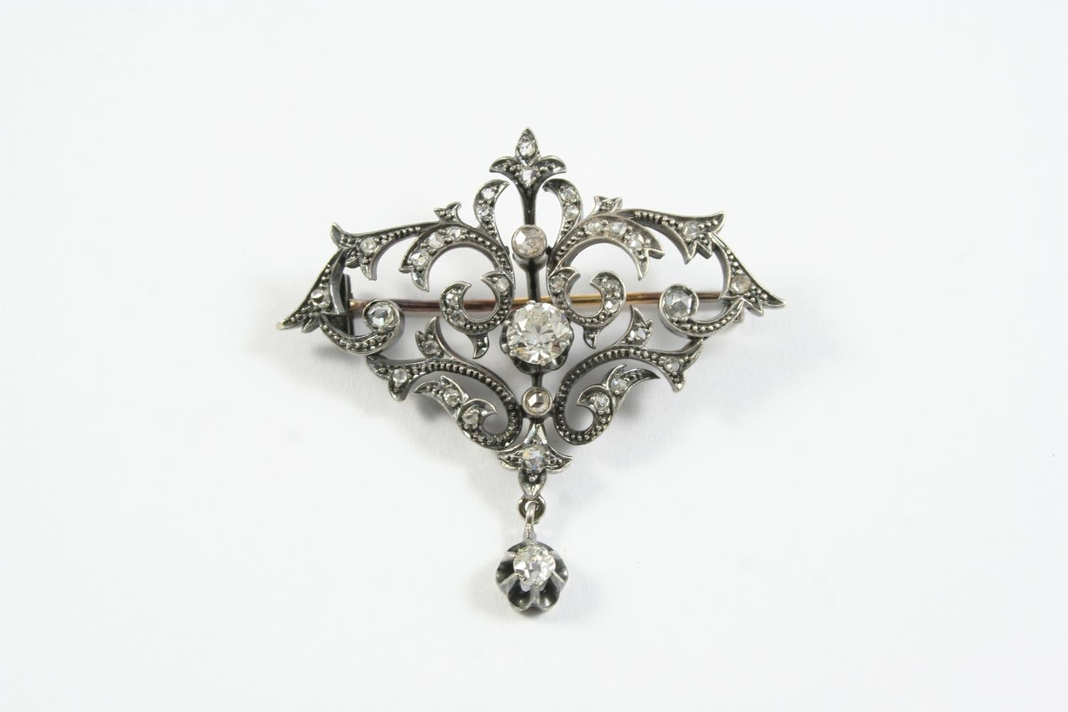 A VICTORIAN DIAMOND BROOCH the scrolling openwork mount is centred with an old circular-cut diamond,