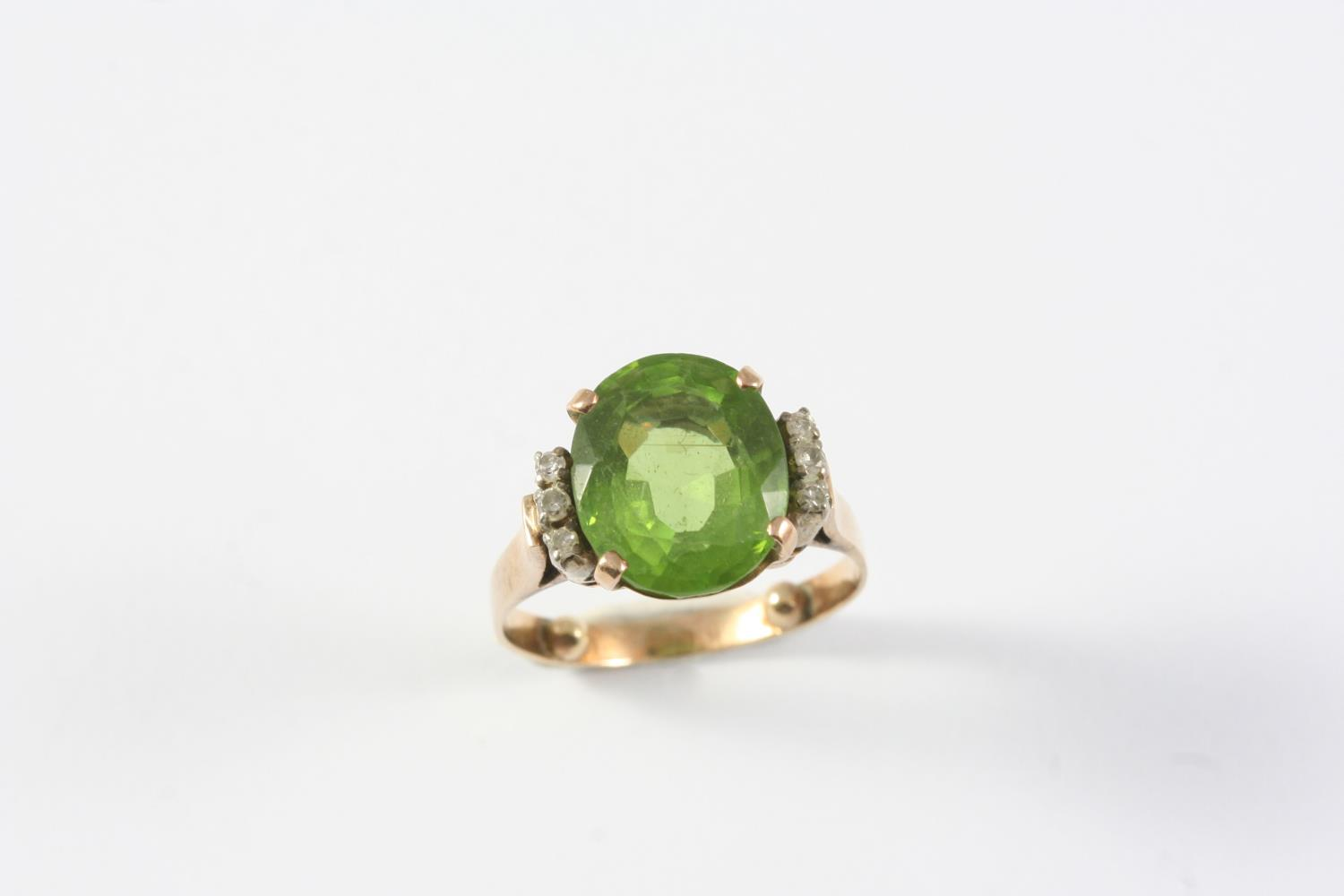 A PERIDOT AND DIAMOND RING the oval-shaped peridot is set with three circular-cut diamonds to each