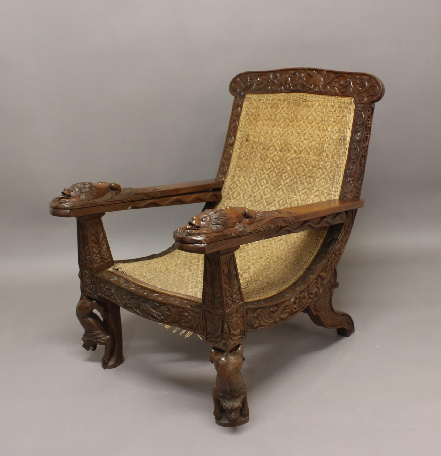 A LATE 19TH/EARLY 20TH CENTURY TEAK PLANTERS CHAIR. A teak planters chair with elaborately carved