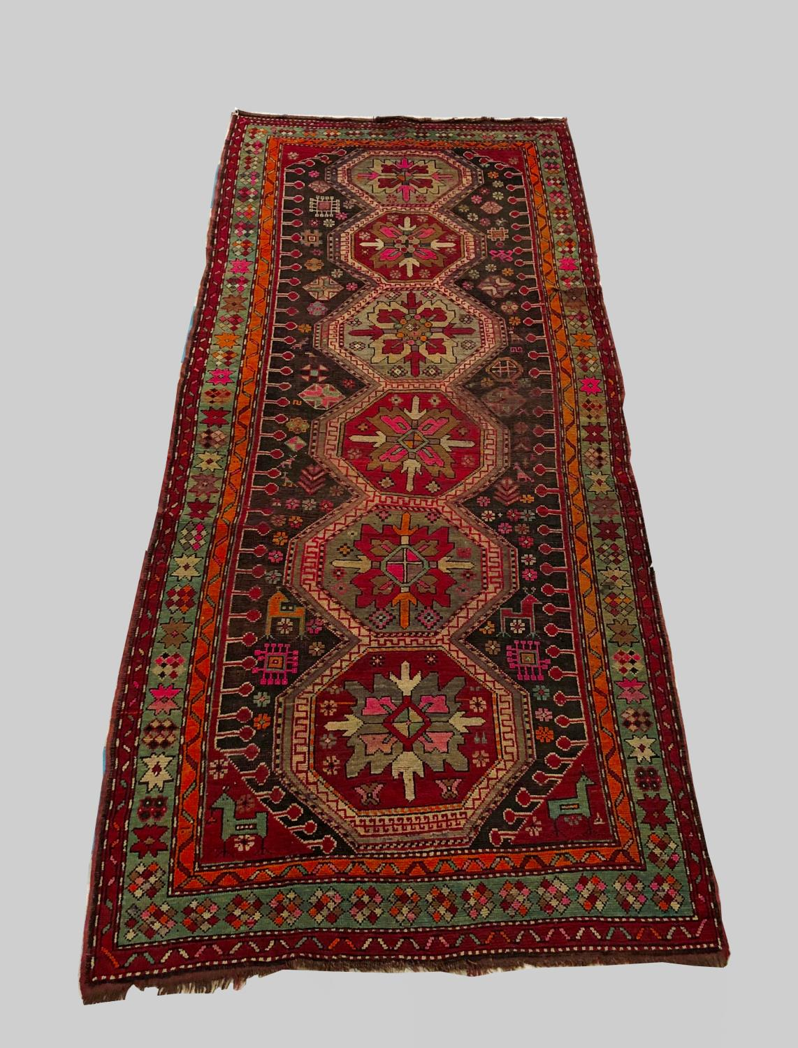 A KARABAGH RUG, South Caucasus, c.1910, the charcoal field with a column of linked octagons