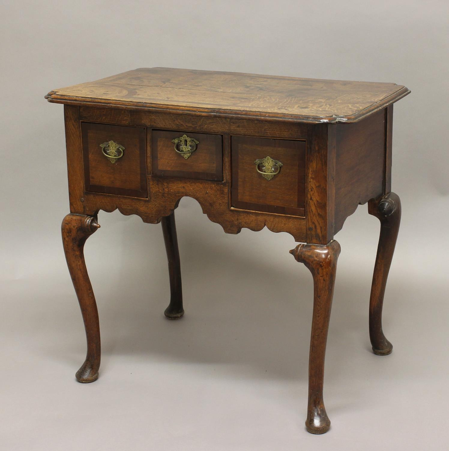 AN 18TH CENTURY OAK LOWBOY, the inlaid shaped rectangular top above three drawers on a carved