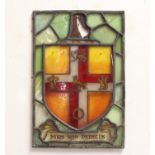 A STAINED GLASS ARMORIAL PANEL, with a shield shaped armorial featuring a lion passant, two