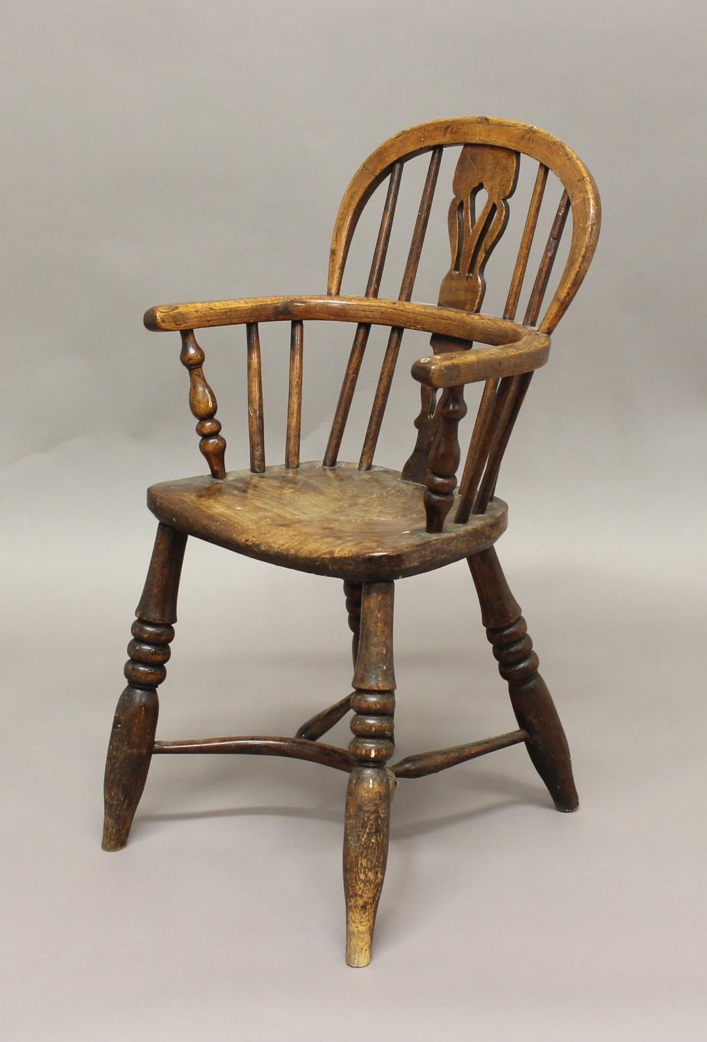 A VICTORIAN CHILD'S BEECH AND ELM WINDSOR ARMCHAIR, with a hooped back and shaped arm rail, with a