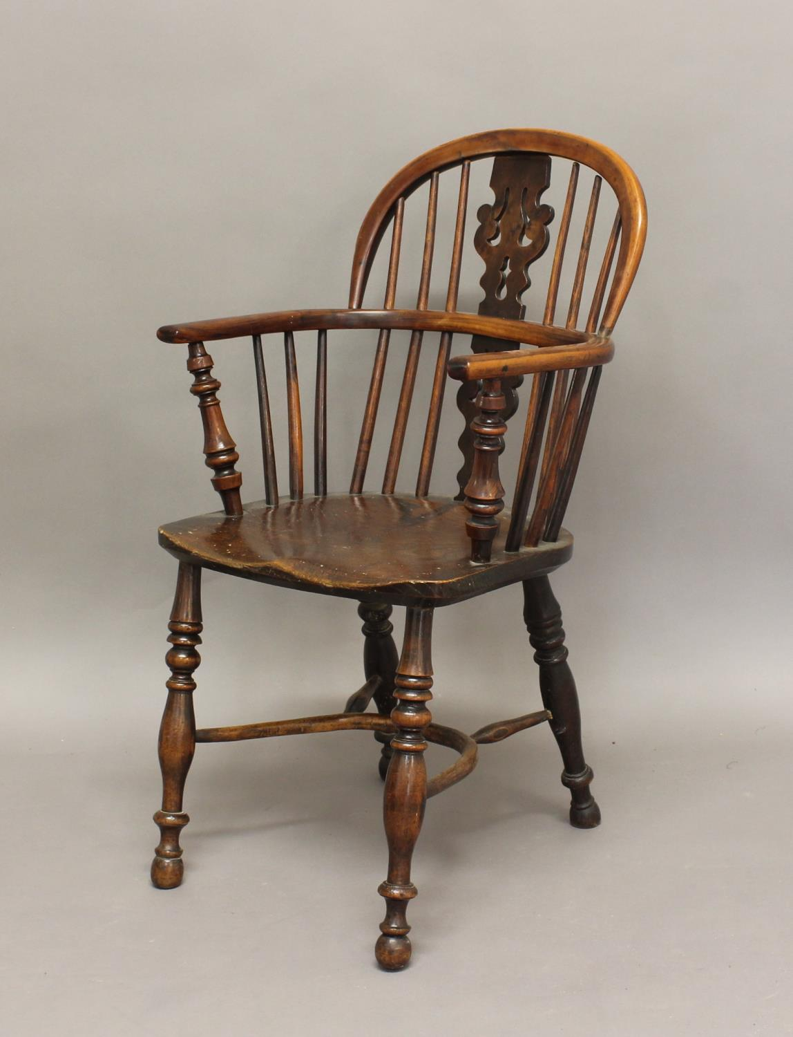 A YEW AND ELM WINDSOR CHAIR, the arched back with pierced splat on turned supports with crinoline