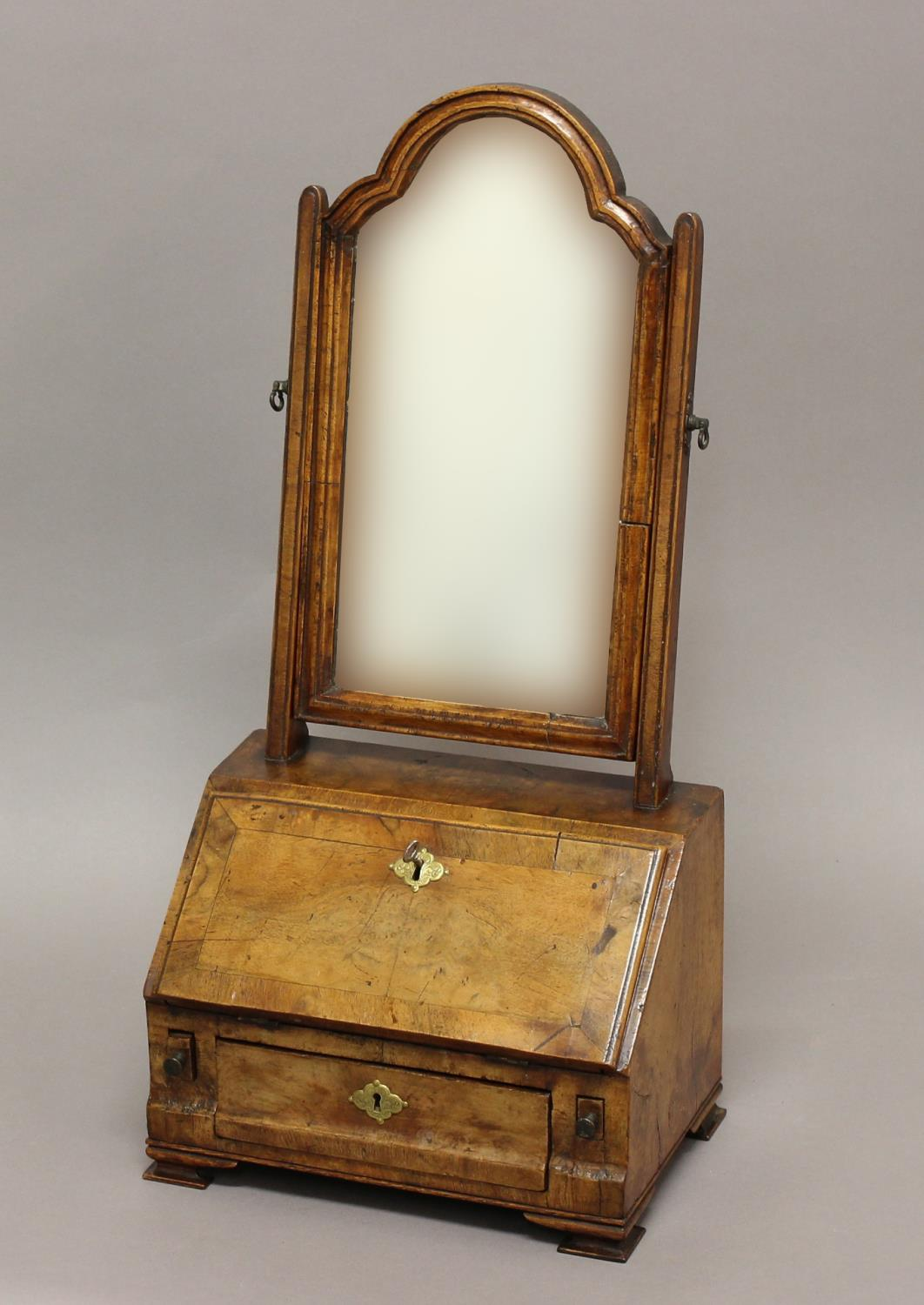 A QUEEN ANNE WALNUT TOILET MIRROR, the shaped mirror above a fitted bureau base with three