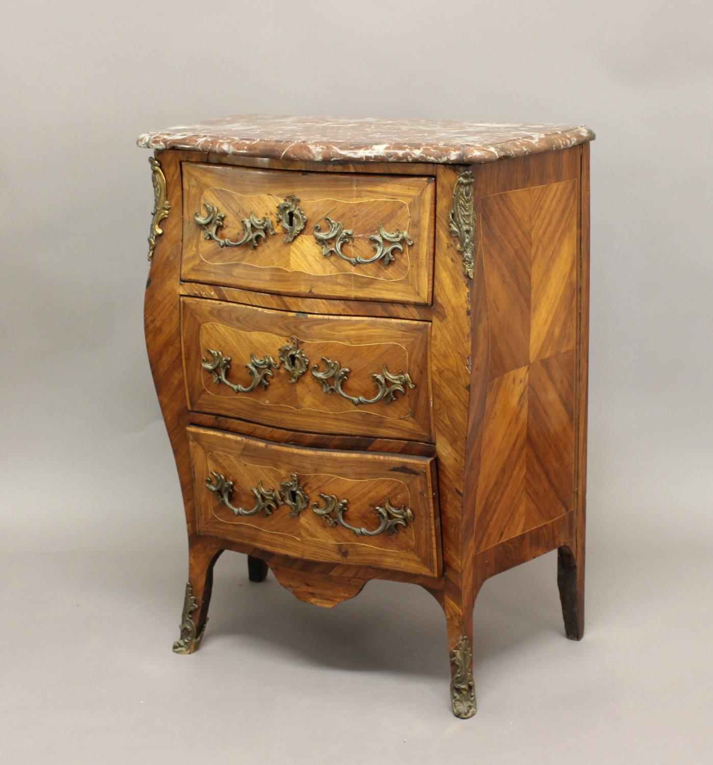 A LOUIS XV STYLE BOMBÉ MARBLE-TOPPED COMMODE, the pink marble top above three drawers with scrolling