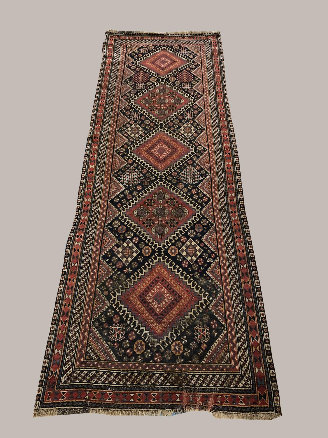 A KASHGAI RUNNER, South West Iran, c.1900, the midnight blue field with single column of latch