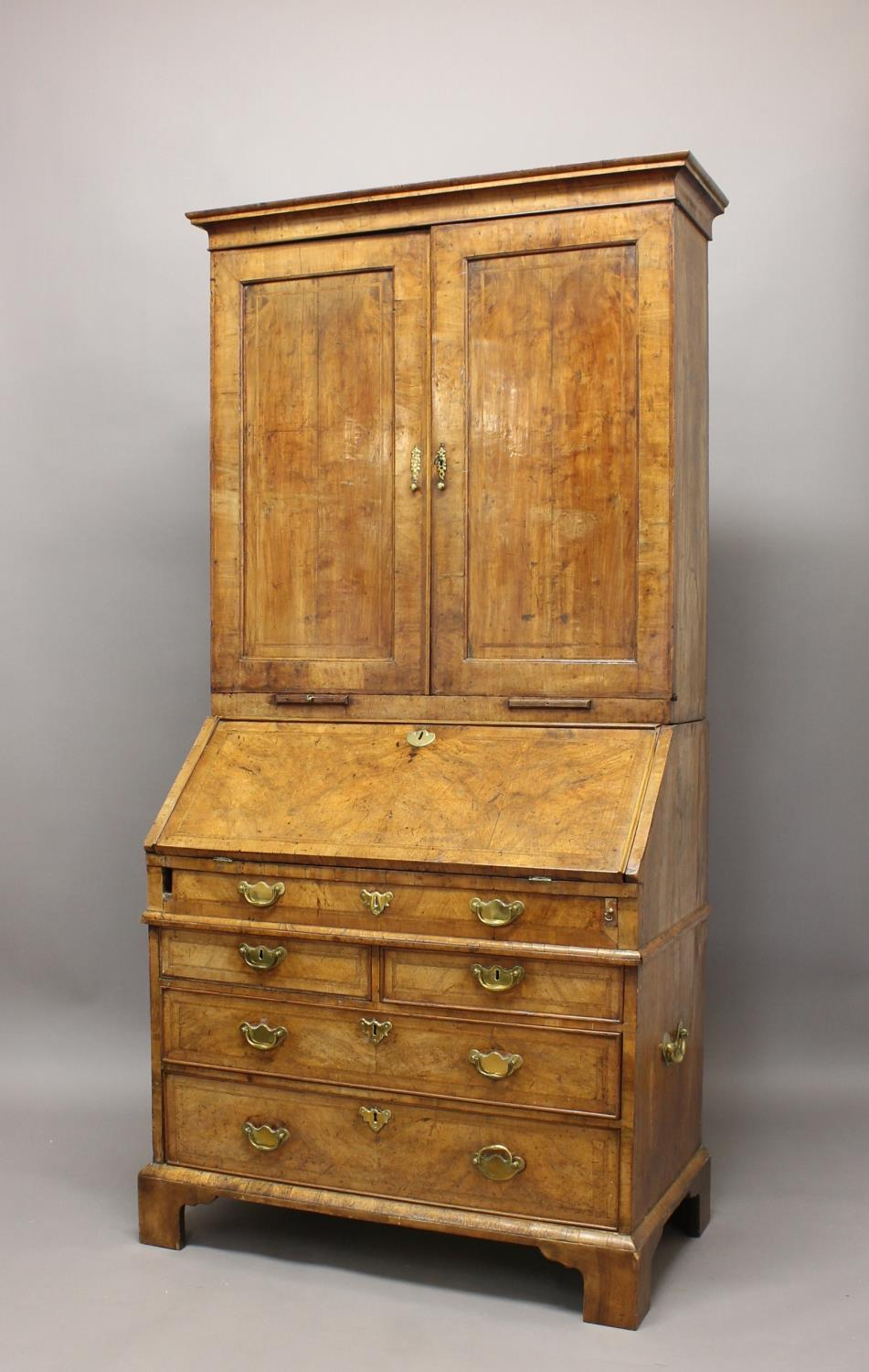 A GEORGE I WALNUT BUREAU CABINET. The upper section with a moulded cornice above twin panelled doors