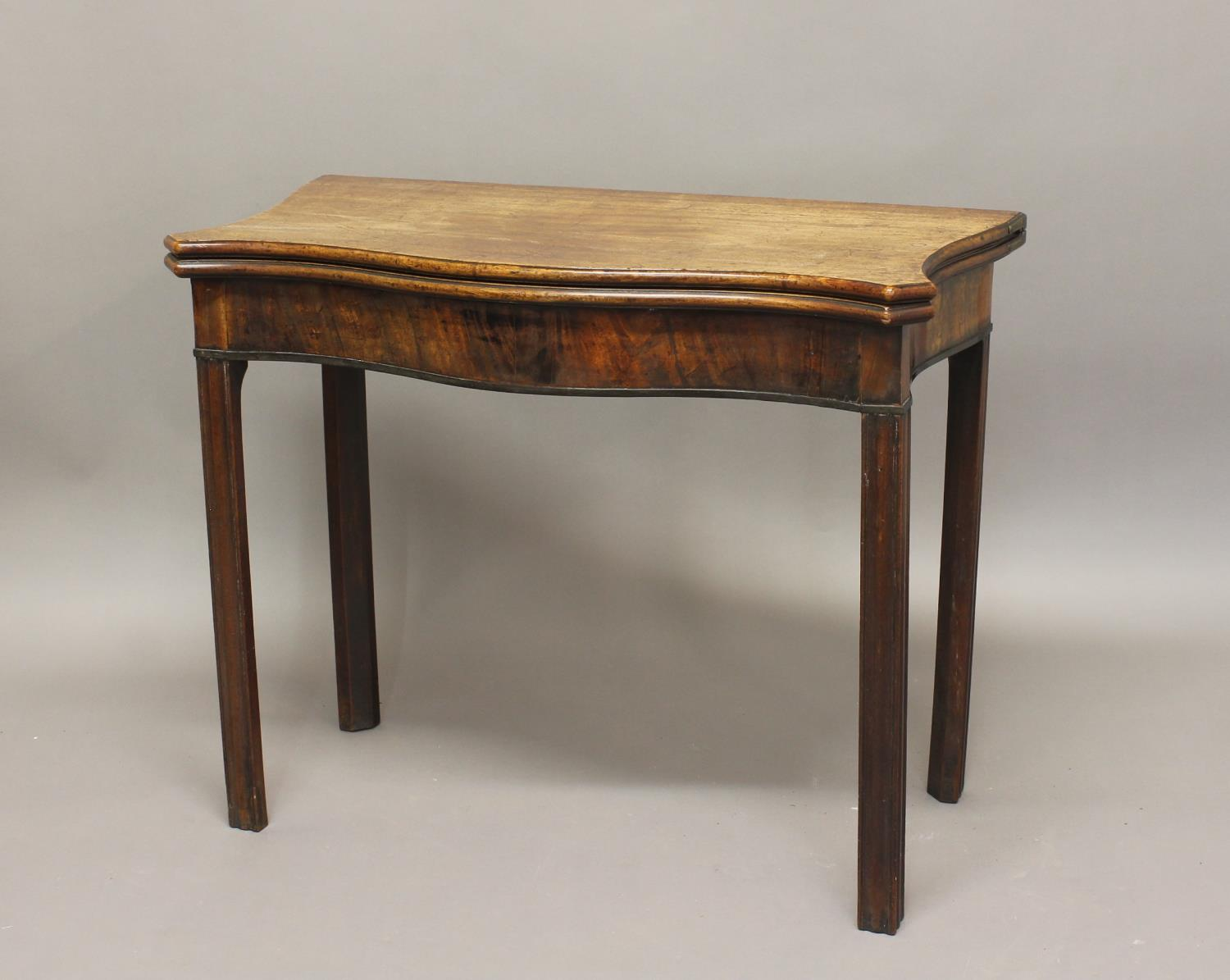 A GEORGE III MAHOGANY TEA TABLE. The serpentine fronted top with shaped sides, enclosing a