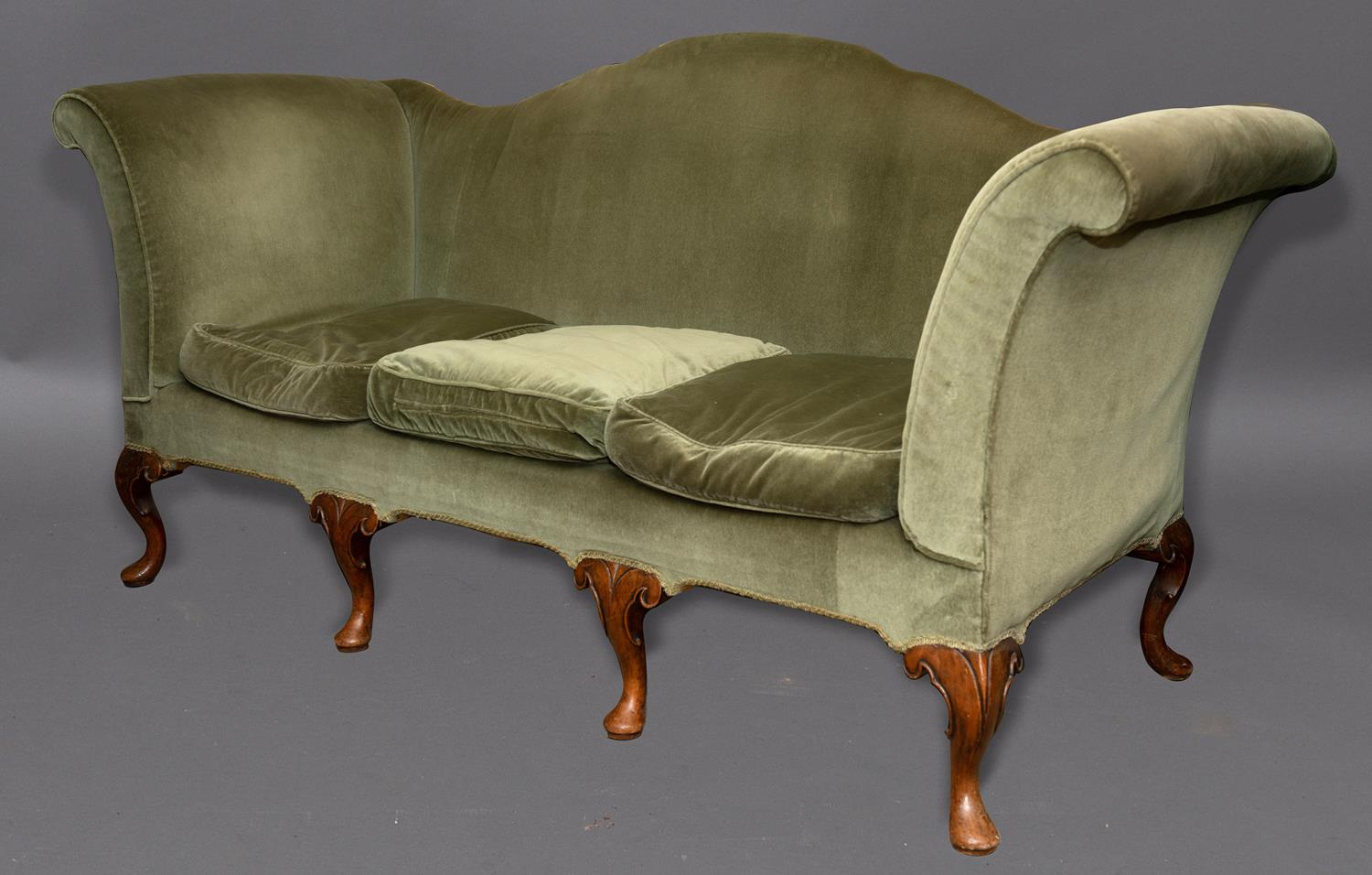 A QUEEN ANNE STYLE THREE SEATER SETTEE. The settee upholstered in green velvet with an arched and