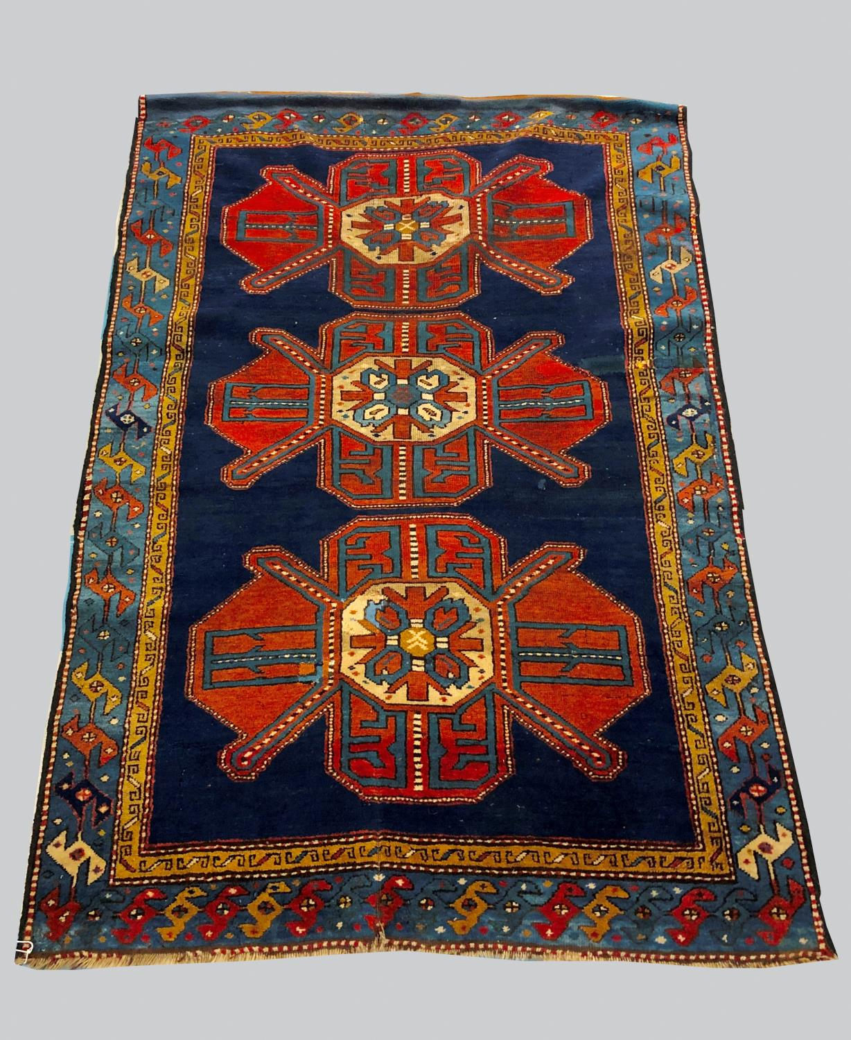 A KAZAK RUG, Central Caucasus, c.1910, the royal blue field with three madder medallions enclosed by