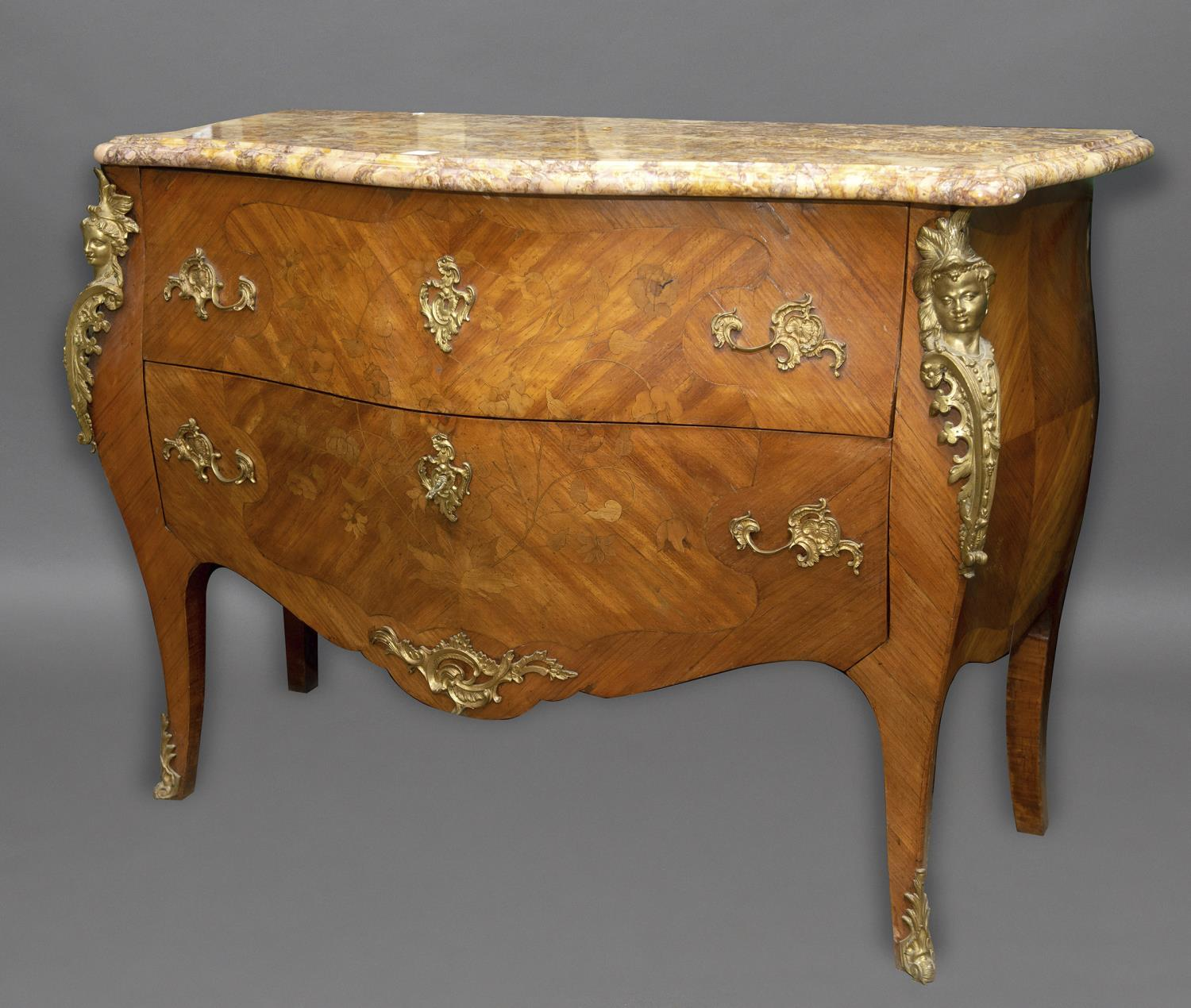 A LOUIS XVI STYLE MARBLE TOPPED COMMODE. The variegated marble top with serpentine front and moulded