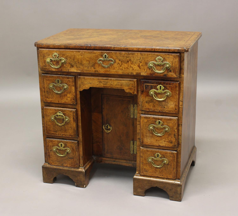 AN EARLY 18TH CENTURY BURR WALNUT VENEERED KNEEHOLE DESK. A kneehole desk with a rectangular cross