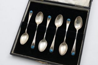 A CASED SET OF SIX GEORGE V HANDMADE COFFEE SPOONS with a hammered finish, the terminals with an