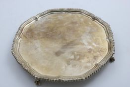 A GEORGE V SALVER of shaped circular outline with a gadrooned border and ball & claw feet, by
