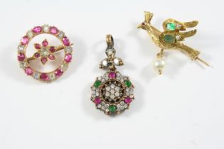 A GOLD AND GEM SET BIRD BROOCH mounted with two emeralds and suspending an untested pearl drop,