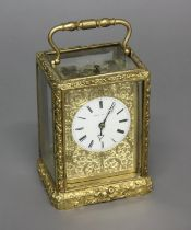 AN ELABORATE GILT BRASS CARRIAGE CLOCK BY HENRY OF PARIS. With a white enamelled dial with Roman