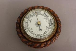 AN OAK FRAMED BAROMETER BY ADIE OF WESTMINSTER. With a carved 'rope twist' surround and decorative