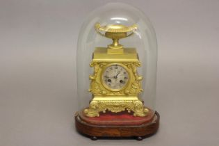 A REGENCY GILT BRASS MANTLE CLOCK AND GLASS DOME. The clock with a silvered dial with engine