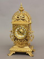 A VICTORIAN GILT BRASS MANTEL CLOCK. The elaborate pierced scrolling case containing a central