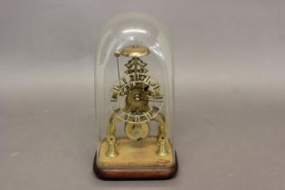 A BRASS SKELETON CLOCK BENEATH A GLASS DOME. A skeleton clock with fretted silvered chapter ring