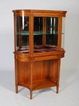 A late 19th century satinwood and ebony lined display cabinet on stand, the moulded cornice above