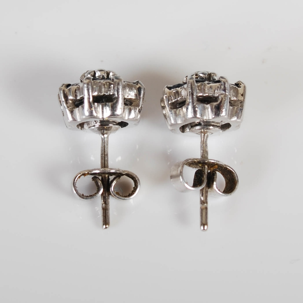 A pair of white metal sapphire and diamond set cluster earrings, circa 1970, each centred with a - Image 2 of 3