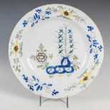 An 18th century Delft charger, decorated with garden of peony in the Fazackerly palette, 35cm