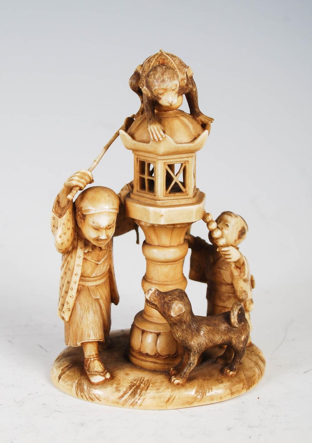 A Japanese ivory okimono of monkey lantern lighter, boy and dog, Meiji Period, signed, 8cm high.