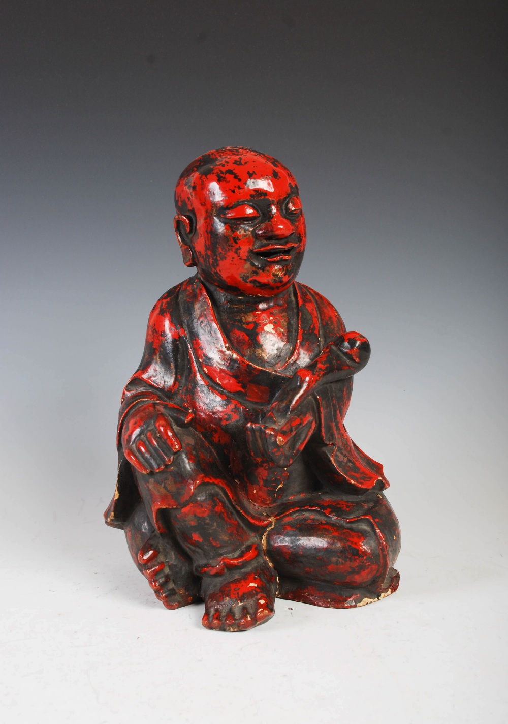 A Chinese carved camphor wood and red lacquered figure of a boy, Qing Dynasty, carved holding a ruyi