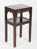 A Chinese dark wood urn stand, Qing Dynasty, the rectangular panelled top above a pierced frieze