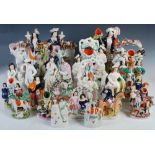 A collection of twenty-three Staffordshire flatback pottery figures, to include; 'DOG TRAV', 30cm